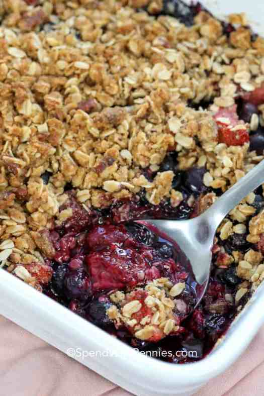 A mixed berry crisp in a white casserole dish with a serving being scooped out.