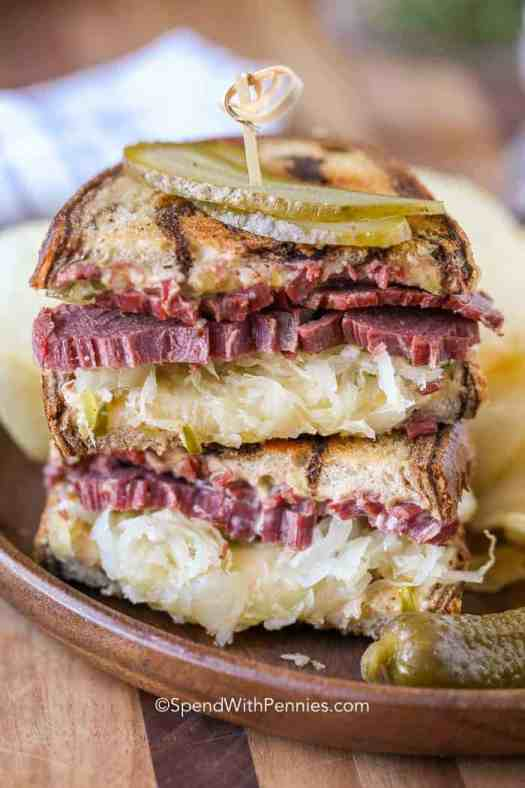 A reuben sandwich stacked on a wooden plate with a skewer in it.