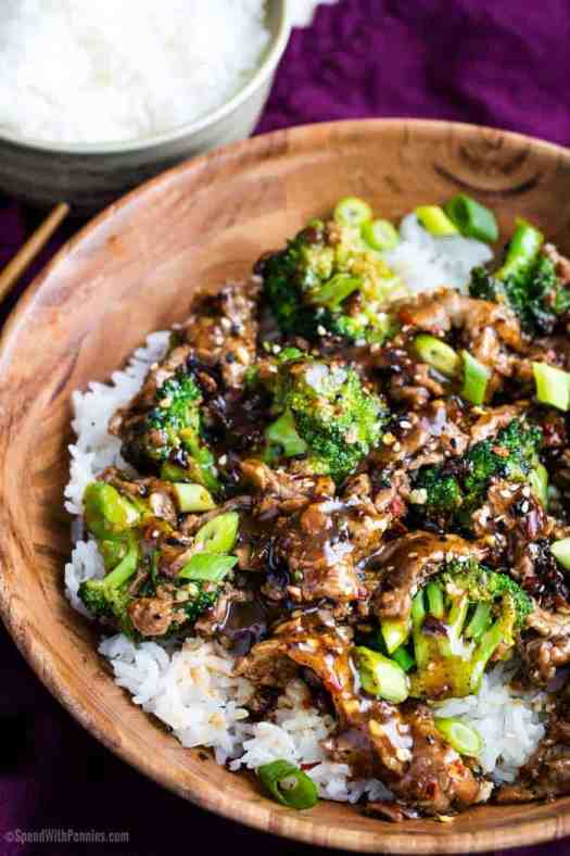 Bowl of beef and broccoli with rice in a wooden bowl and rice on the side