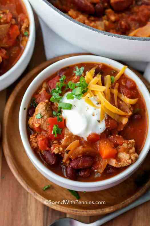 A bowl of turkey chili topped with sour cream, green onions, and shredded cheddar cheese.