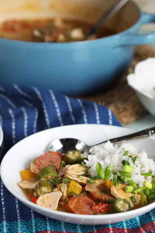 Chicken gumbo with white rice in a white bowl on a blue striped napkin.