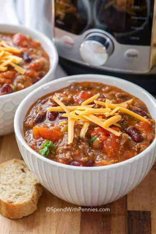 Two bowls of Instant Pot chili topped with cheese with an Instant Pot in the background and a baguette slice next to them.