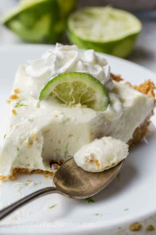 Slice of key lime pie on a plate with a bite missing and a spoon of key lime pie