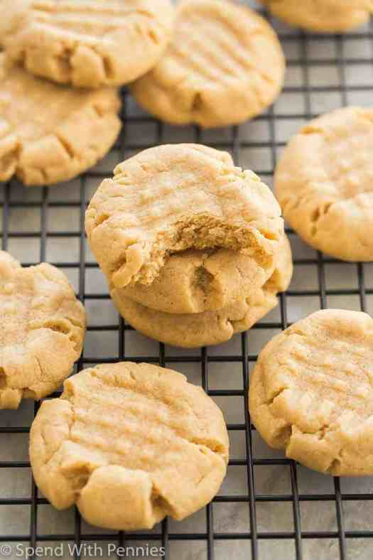 Peanut butter cookies stacked on a cooling rack with a bite out of one cookie