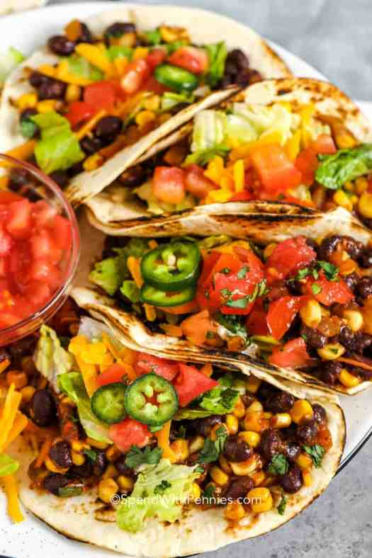 Four black bean tacos prepared on a plate. Topped with lettuce, tomatoes, cheese, and jalapenos.