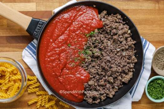 Meat sauce in a pan with parsley and a jar of fusilli pasta