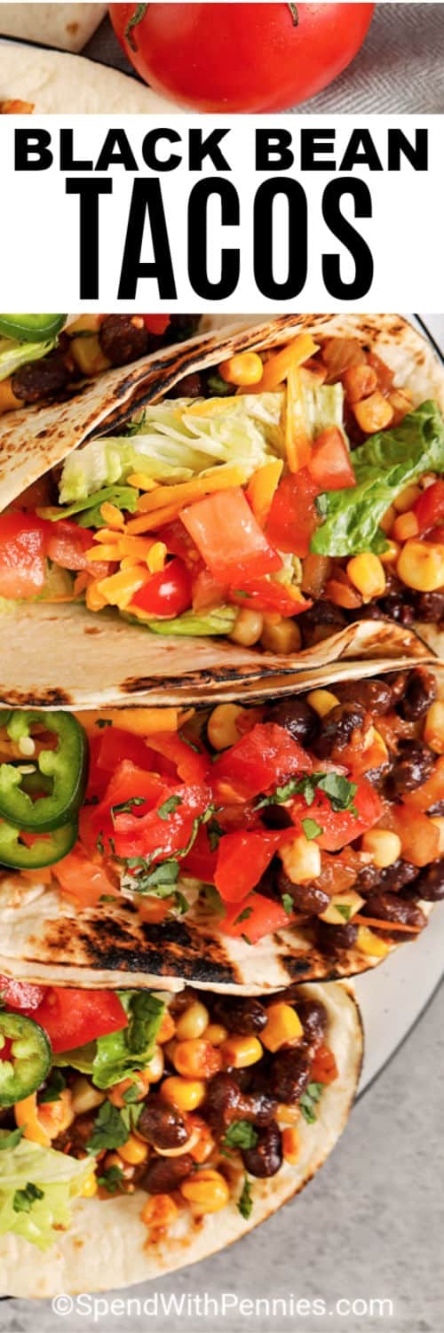 Close up of a black bean taco topped with lettuce, tomatoes, and jalapeños.