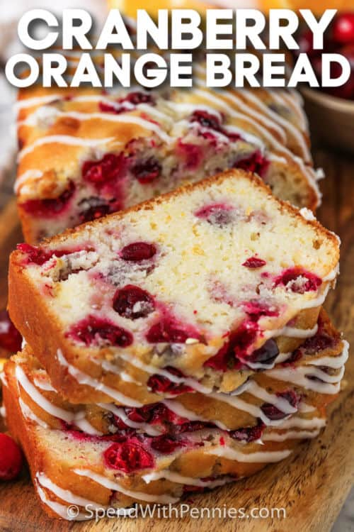Cranberry Orange Loaf sliced on a cutting board with writing