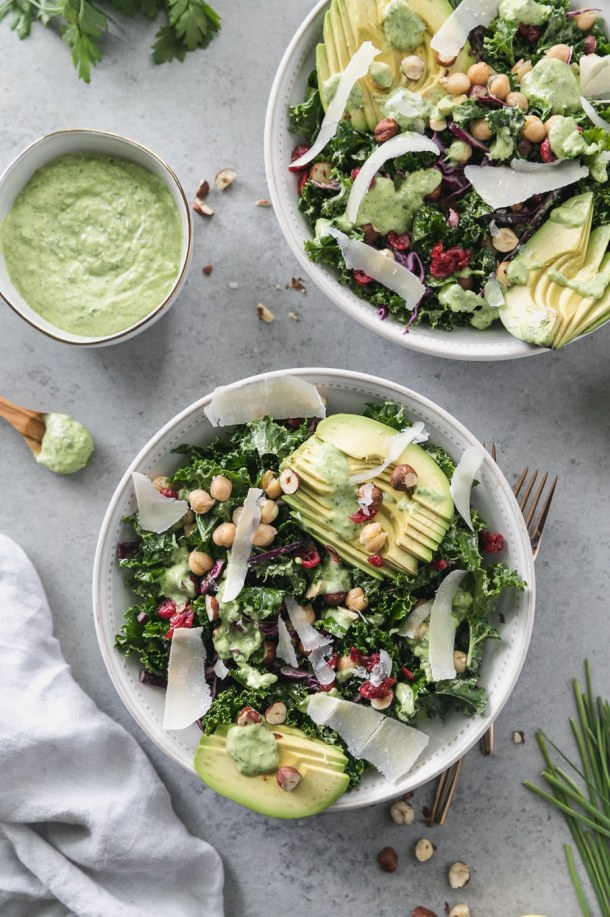 Overhead shot of a kale salad topped with sliced avocado, parmesan shavings, hazelnuts, chickpeas, and dried cranberries