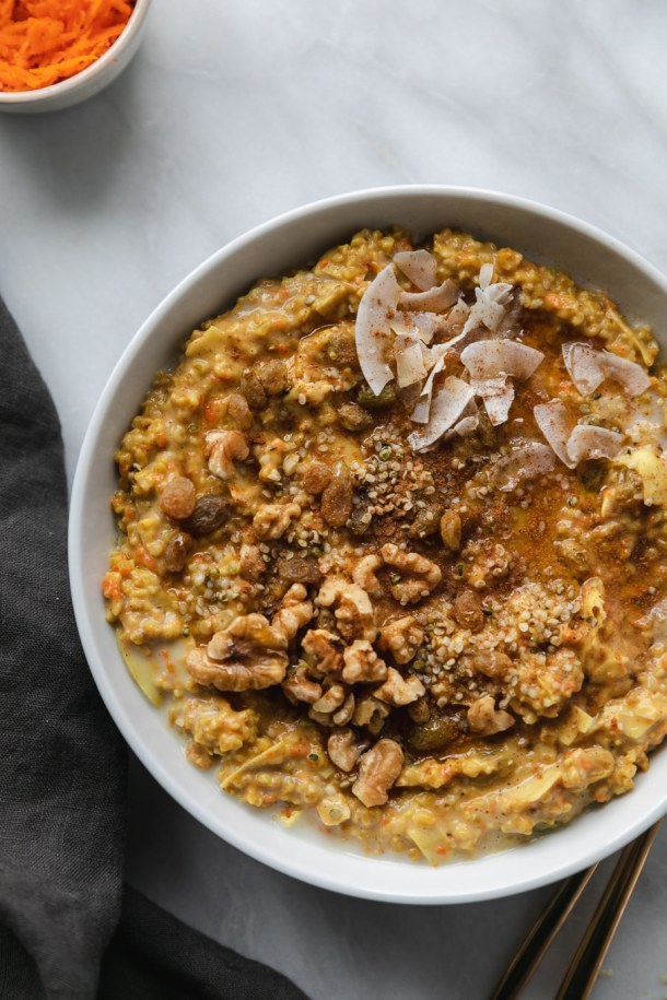 Overhead close up shot of a bowl of carrot cake oatmeal garnished with coconut flakes, maple syrup, golden raisins, walnuts, and hemp seeds