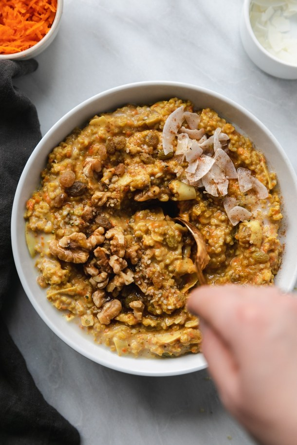 Overhead shot of a bowl of carrot cake oatmeal and a hand stirring it with a gold spoon