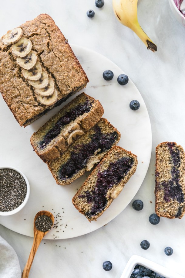 Overhead shot of a loaf of blueberry chia jam stuffed banana bread with 4 slices cut off and a bowl of chia seeds next to it
