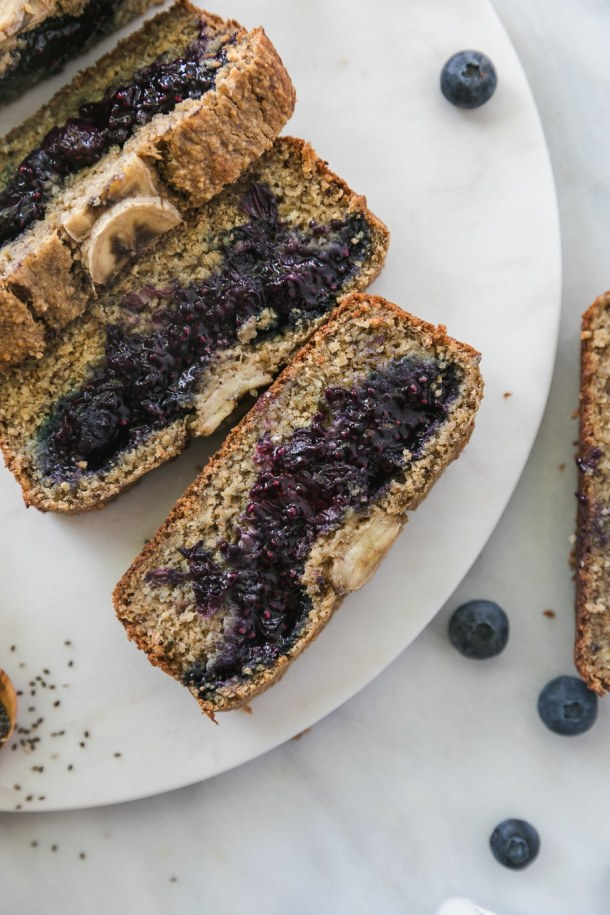 Overhead shot of a loaf of blueberry chia jam stuffed banana bread with 3 slices cut off