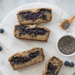 Overhead shot of slices of blueberry chia jam stuffed banana bread on a circular marble board