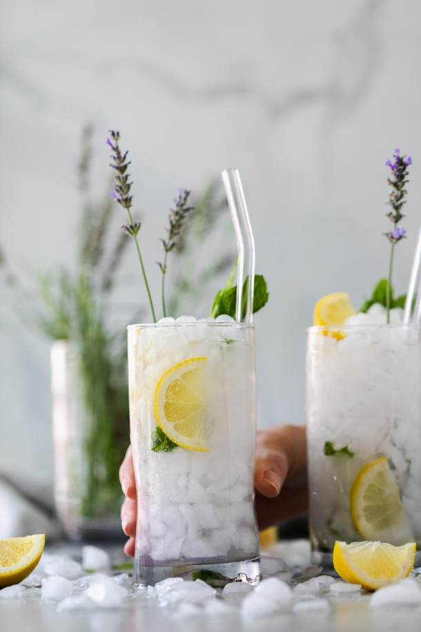 Forward facing shot of 2 lavender mint cocktails with a hand grabbing one
