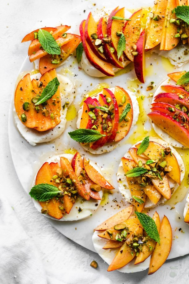Overhead shot of peach caprese with pistachios and mint