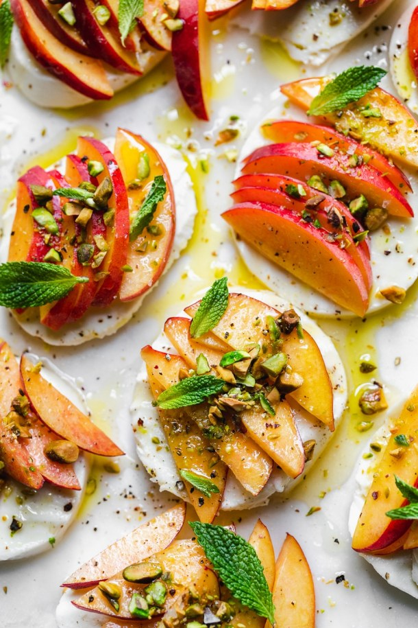 Overhead close up shot of peach caprese with pistachios and mint