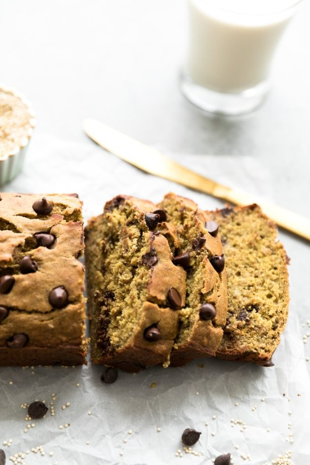 Shot of a loaf chocolate chip banana bread with a few slices cut off and a gold knife in the background