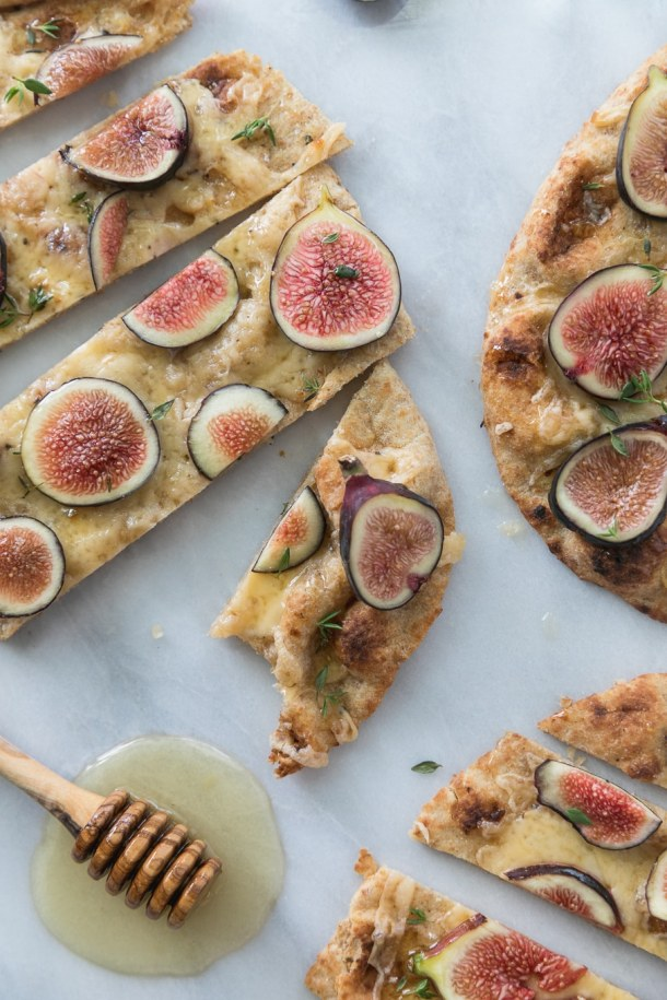 Overhead close up shot of a fig flatbread sliced into pieces with a bite taken out of one piece