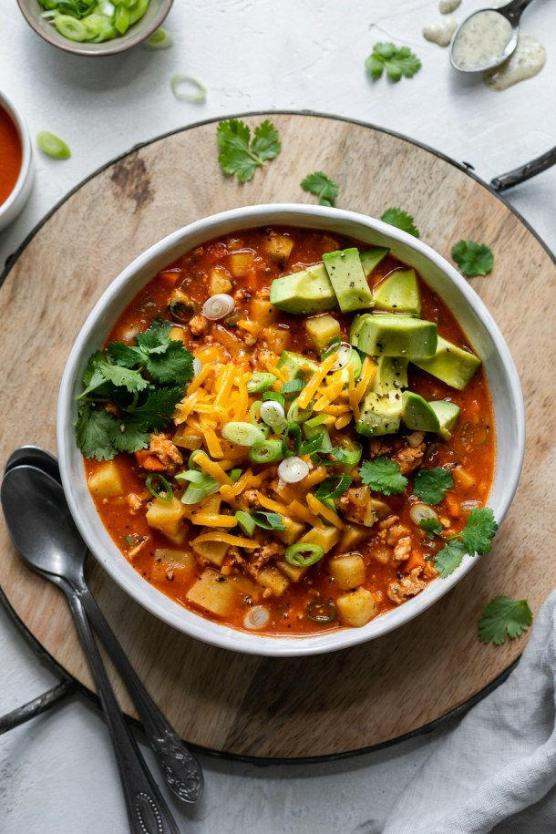 Overhead shot of a bowl of chili topped with cheese, cilantro, and avocado