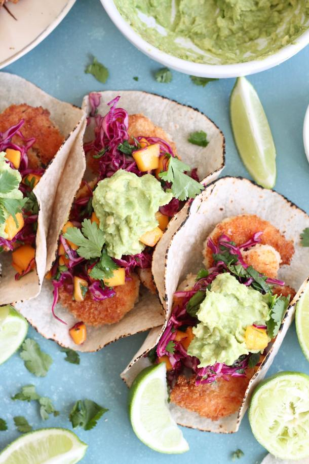 Overhead closeup shot of coconut shrimp tacos topped with mango sweet chili slaw and avocado mash