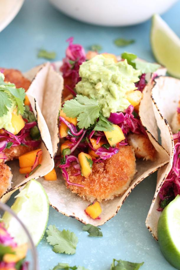 Closeup shot of coconut shrimp tacos topped with mango sweet chili slaw and avocado mash