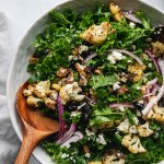 Overhead close up shot of a bowl of kale salad with roasted cauliflower, red onion, feta, dried cherries, and walnuts with a large wooden salad spoon in the bowl