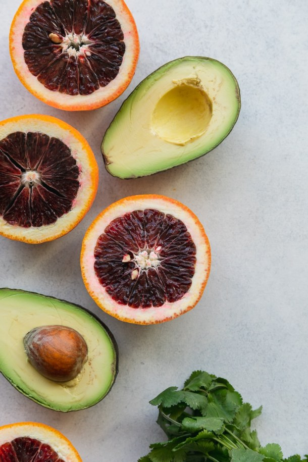 Overhead close up shot of halved avocados and halved blood oranges