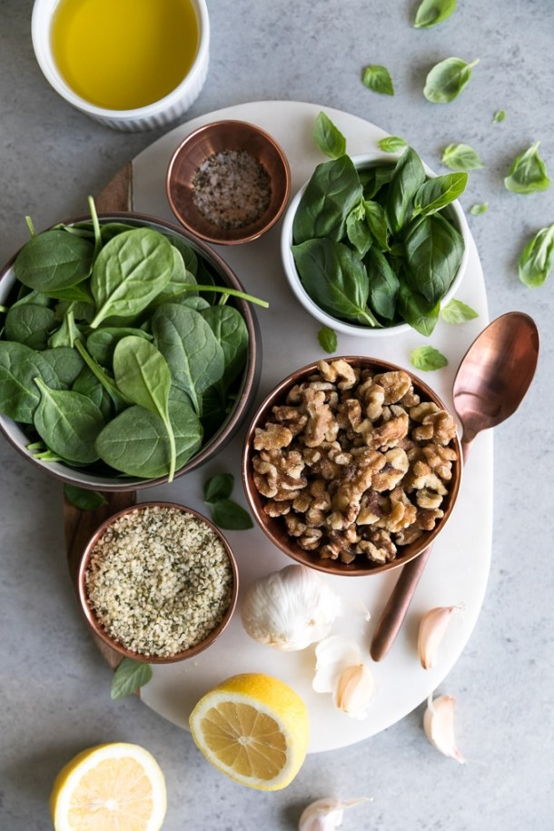 Overhead shot of a bowls of spinach, basil, walnuts, hemp seeds, and salt and pepper with a head of garlic and a halved lemon below them