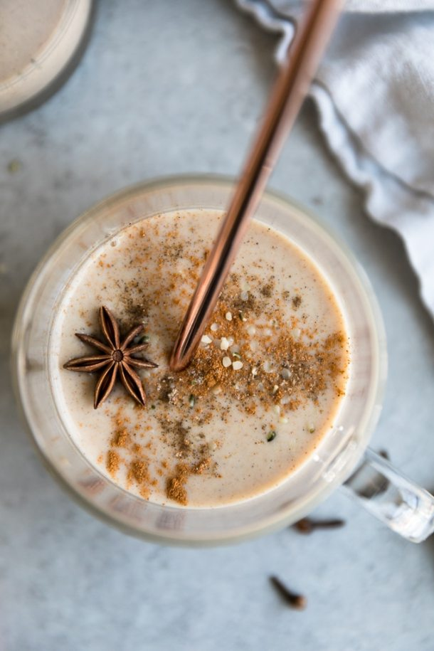 Overhead shot of a chai smoothie in a clear glass with a handle with cinnamon and a star anise pod on top and a bronze straw sticking out