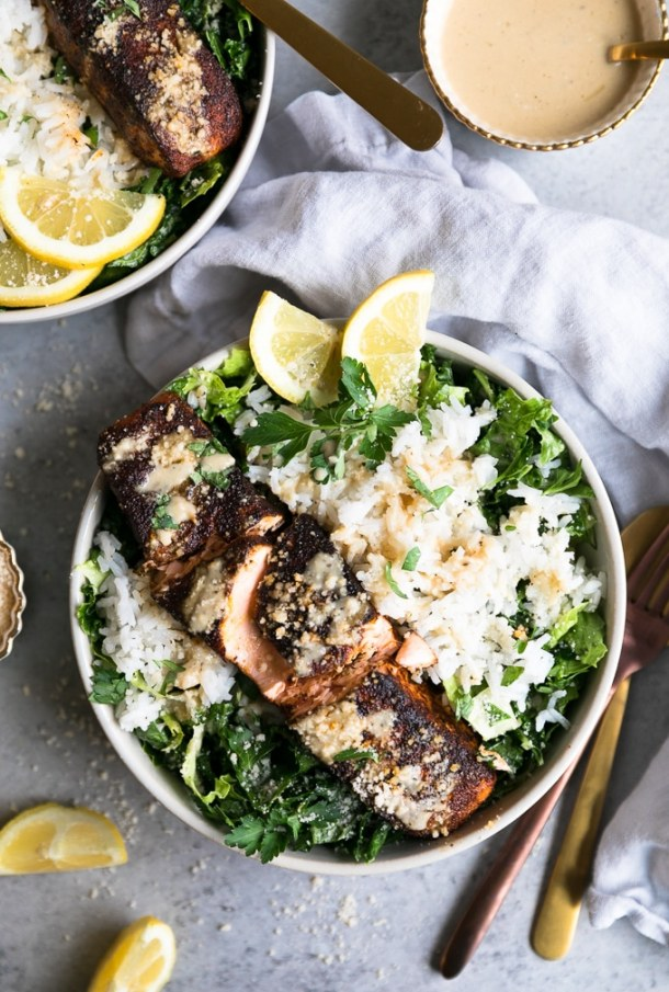 Overhead close up shot of a bowl of salad with rice, a salmon filet, and another bowl in the top left as well as a ramekin of caesar dressing in the top right of the frame