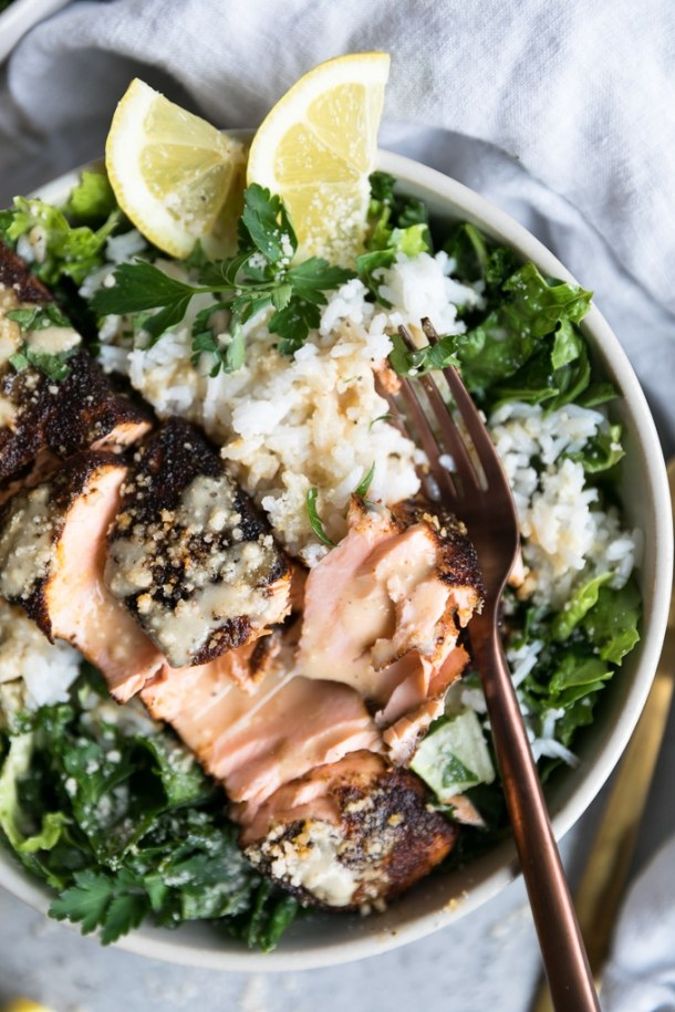 Overhead close up shot of a bowl of salad with rice, a broken apart salmon filet, and a fork resting on it