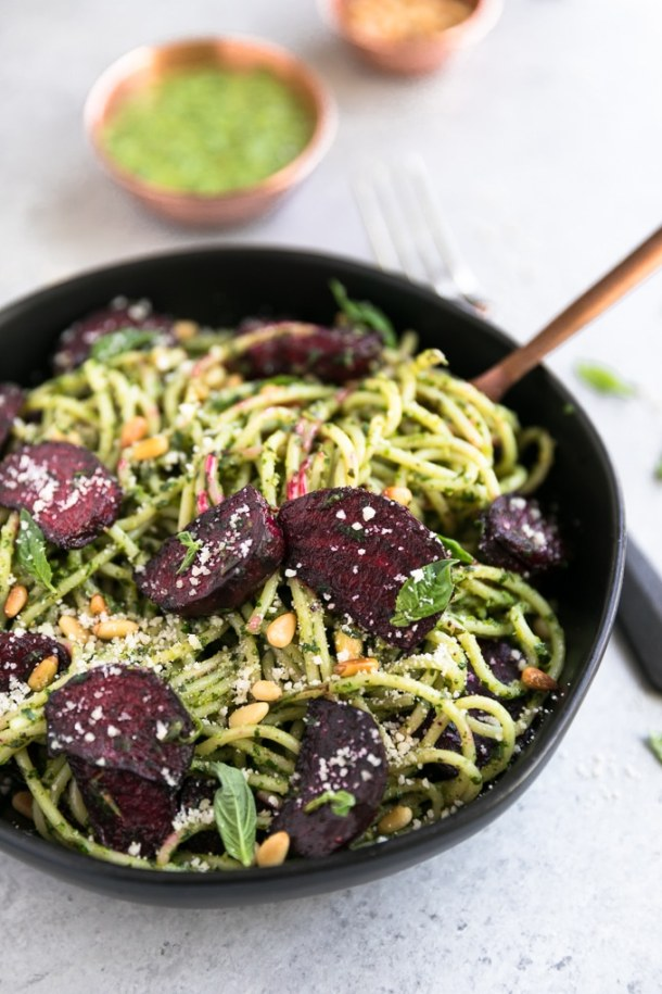 Close up shot of a bowl of pesto pasta with roasted beets and toasted pine nuts with a fork twirling the pasta