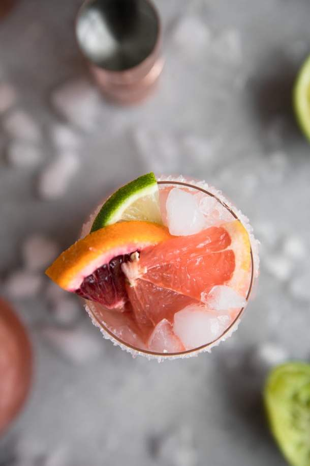 Overhead shot of a cocktail with a grapefruit slice, blood orange slice, and lime slice peeking out
