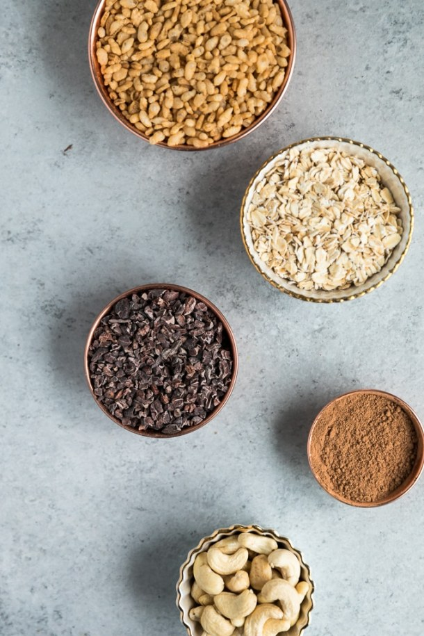 Overhead shot of a bowl of puffed rice cereal, a bowl of rolled oats, a bowl of cacao nibs, and a bowl of cacao powder