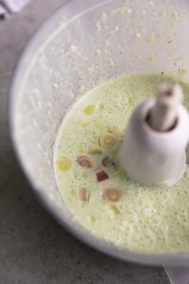 Close up shot of a food processor filled with light green lemongrass sauce