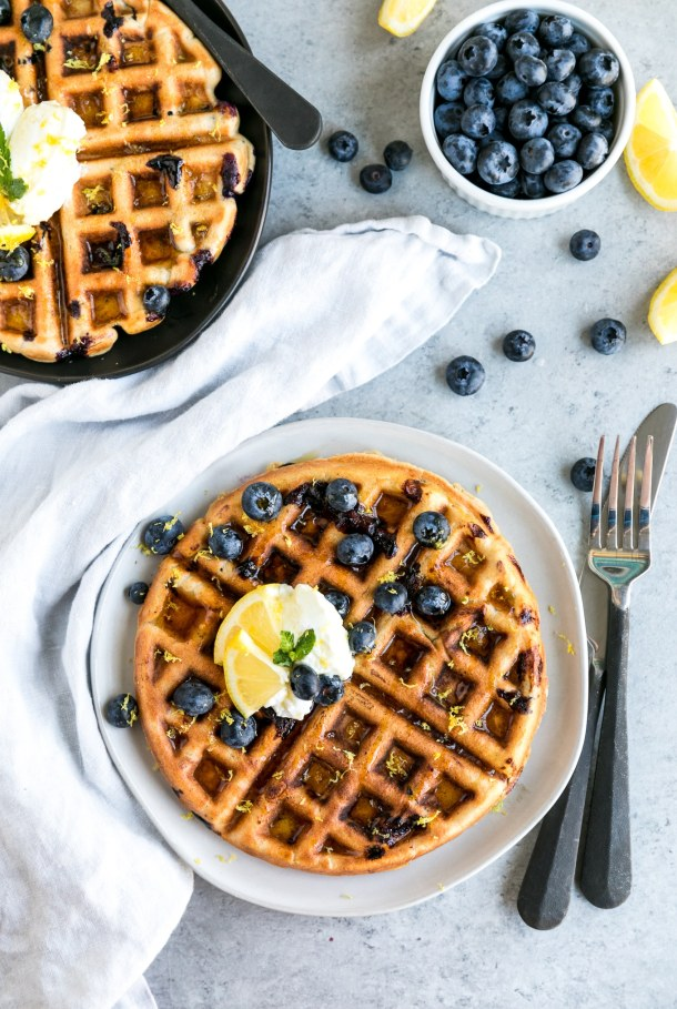 Overhead shot of a waffle with another waffle sticking out in the top left corner and blueberries scattered around