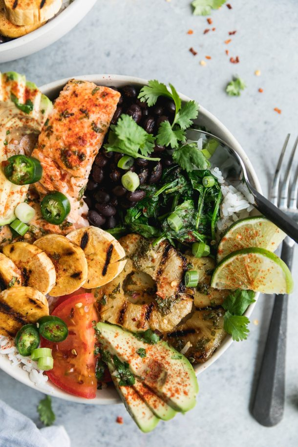 Overhead close up shot of a bowl of salmon with grilled plantains, black beans, grilled pineapple, lime, tomatoes, and cilantro with a spoon digging in