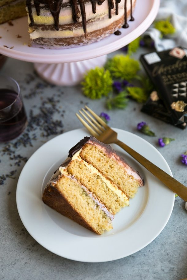 Close up shot of a slice of cake with purple, pink, and yellow icing with a gold fork resting on the plate