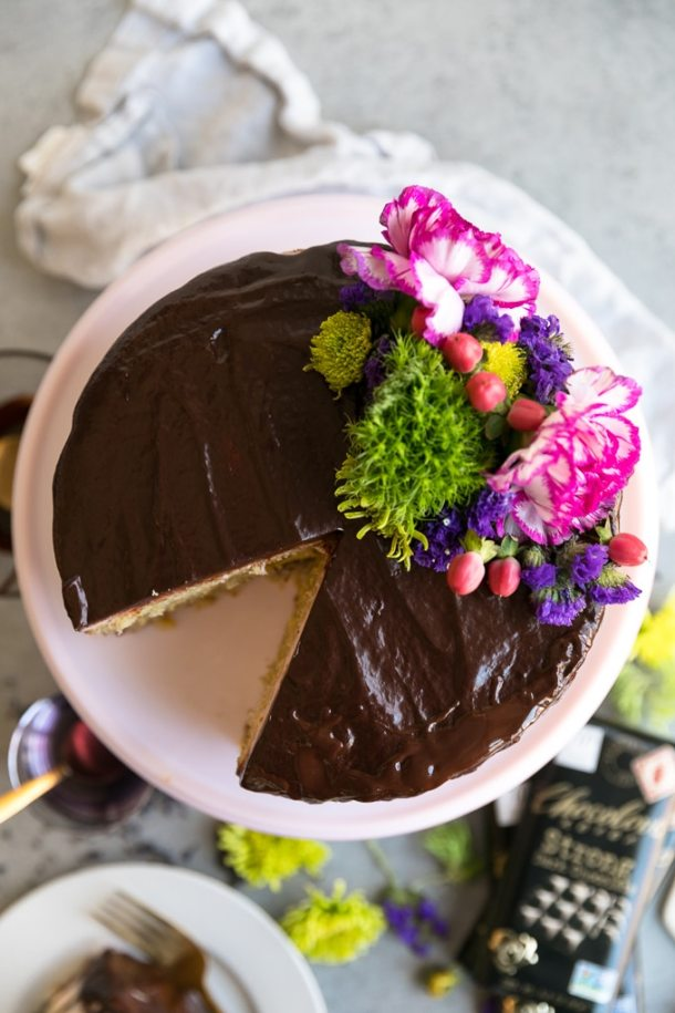 Overhead shot of a cake on a cake stand covered in chocolate ganache and colorful flowers with a slice taken out