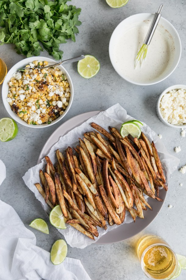 Overhead shot of a plate of golden brown fries, with a bowl of Mexican street corn and lime wedges