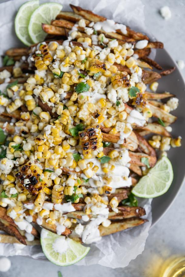 Overhead close up shot of fries topped with Mexican street corn, crumbled cotija cheese, cilantro, and crema