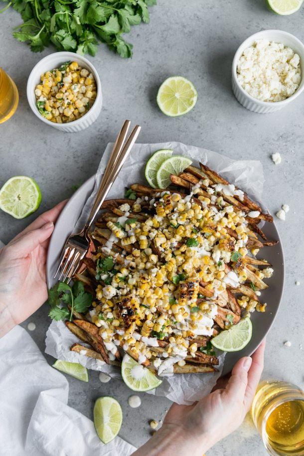 Overhead shot of fries topped with Mexican street corn, crema, lime wedges, and cilantro, with a fork and spoon resting on the plate, and two hands reaching out holding the plate