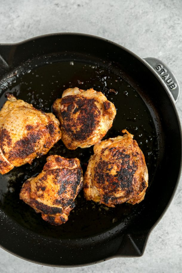 Overhead shot of seared chicken thighs in a cast iron skillet