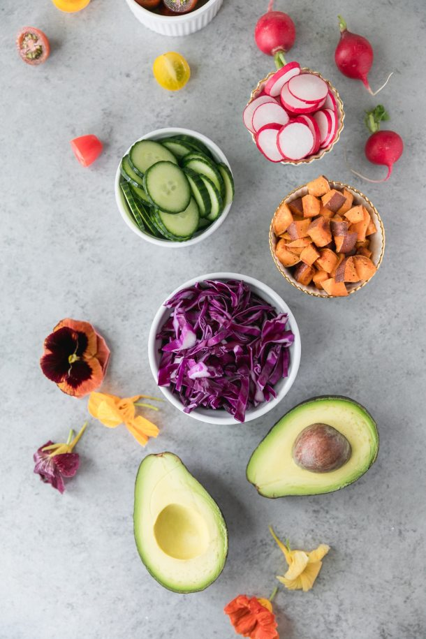 Overhead shot of bowls of sliced radishes, cucumber, roasted sweet potato, and red cabbage, with a halved avocado and edible flowers