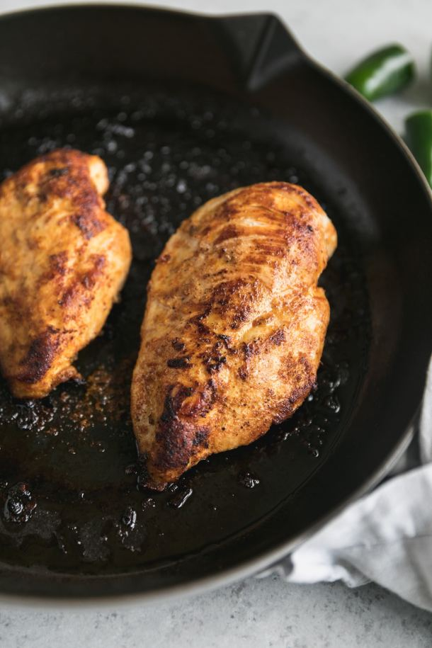Close up shot of a golden brown chicken breast cooked in a cast iron skillet