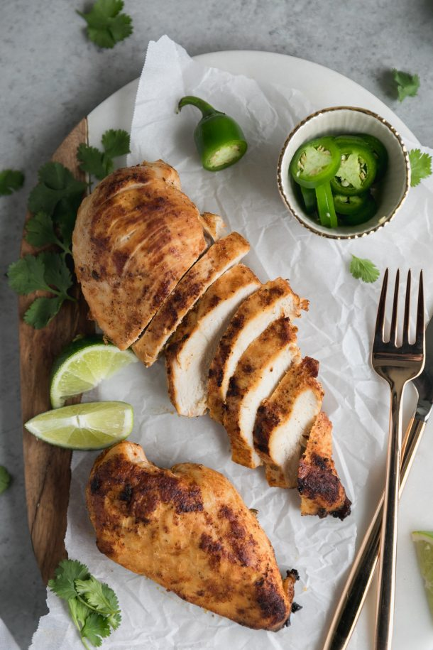 Overhead shot of two chicken breasts, one sliced and one whole, with lime wedges, a bowl of sliced jalapeños, and cilantro off to the side, and a gold fork and knife to the right