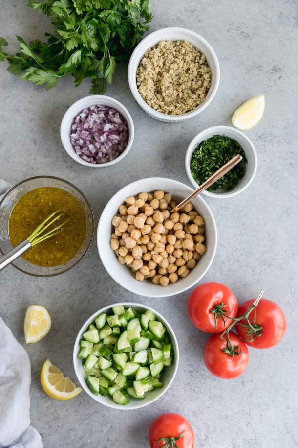 Overhead shot of bowls of chickpeas, red onion, quinoa, shopped parsley, diced cucumber, and salad dressing, with a bunch of vine ripe tomatoes in the bottom right of the frame