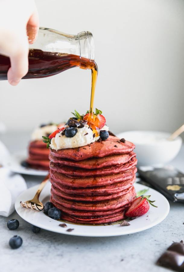 Forward facing shot of a stack of red velvet pancakes topped with whipped cream and berries, with maple syrup being poured over them