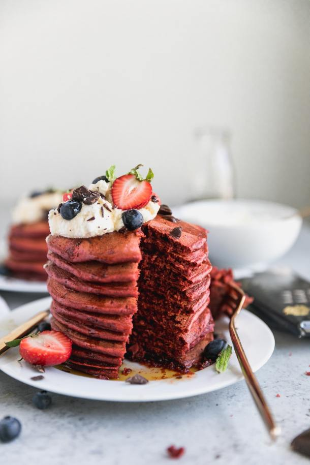 Forward facing shot of a stack of red velvet pancakes topped with whipped cream and berries with a bite taken out of them and another stack of pancakes in the background
